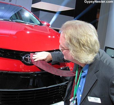David uses his tie to polish the logo on the newly unveiled The 2014 Toyota Corolla