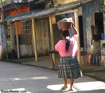 Woman carrying goods atop her head in Livingston, Gualemala